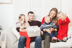 Familj för lycklig jul med ungar som öppnar gåvan royaltyfria foton