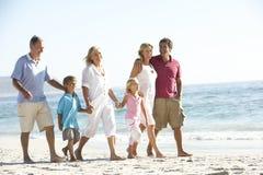 Familj för tre utveckling på ferie som går på stranden arkivfoto
