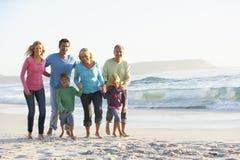 Familj för tre utveckling på ferie som promenerar stranden Arkivfoto