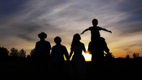 Familj för tre utveckling som går på den ljusa solnedgången lager videofilmer