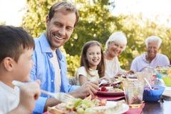Familj för tre utveckling som har lunch i trädgården arkivfoton