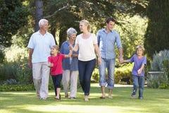 Familj för tre utveckling som tillsammans går i trädgård Royaltyfri Foto