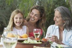 Familj för tre utveckling på den trädgårds- tabellen Arkivbild