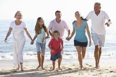 Familj för tre utveckling som har gyckel på stranden Fotografering för Bildbyråer