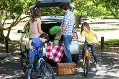 Familj framme av en bil royaltyfri bild