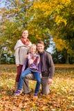 Familj framme av färgrika träd i höst eller nedgång arkivbilder