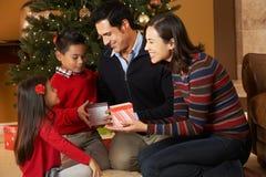 Familj framme av julgranen Arkivfoto