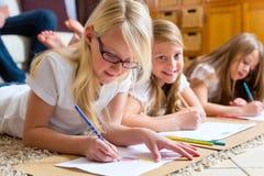 Familj hemma, barnen som färgar på golv Arkivbild