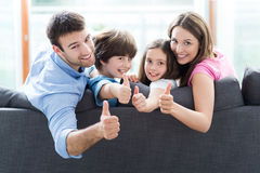 Familj hemma med tummar upp Fotografering för Bildbyråer