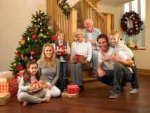 Familj hemma runt om jultree Arkivbild