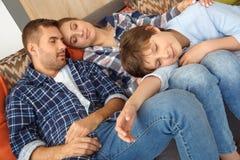 Familj hemma som sitter på soffan i vardagsrum som tillsammans sover trött närbild royaltyfri fotografi