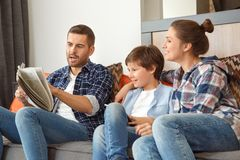 Familj hemma som tillsammans sitter på soffan i för fadervisning för vardagsrum som tidningen chockas till moder- och soninnehave royaltyfria foton