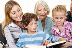 Familj, i att läsa för tre utvecklingar Royaltyfri Bild