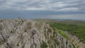 Familj i berg på kanten av en mäktig klippa i Krim lager videofilmer