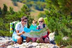 Familj i berg som diskuterar rutten royaltyfria foton