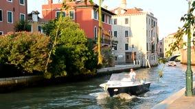 Familj i en motorbåtsegling längs den pittoreska kanal-gatan arkivfilmer