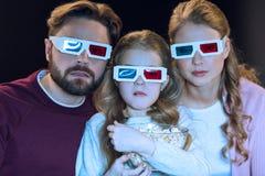 Familj i exponeringsglas som 3d håller ögonen på film- och innehavpopcorn Royaltyfria Bilder