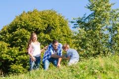Familj i gräs på äng Royaltyfria Bilder