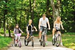 Familj i parken på cyklar Arkivbilder