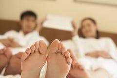 Familj i säng med kal fot Arkivfoton