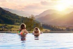 Familj i simbassäng med bergsikt royaltyfria bilder