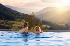 Familj i simbass?ng med bergsikt royaltyfria bilder