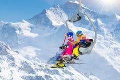 Familj i skidlift i berg Skida med ungar arkivfoto