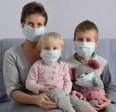 Familj i skyddande maskeringar Arkivfoton