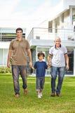 Familj i tre utvecklingar framme av hus Royaltyfri Foto