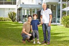 Familj i tre utvecklingar i en trädgård arkivbild