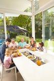 Familj i tre utvecklingar som äter på lunchtabellen Arkivfoto