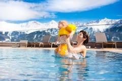 Familj i utomhus- simbassäng av den alpina brunnsortsemesterorten Royaltyfri Bild