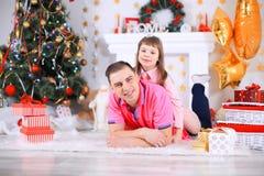 Familj, jul, x-mas, lycka och folkbegrepp - le fadern och den hållande gåvaasken för dotter royaltyfri foto