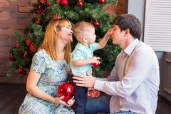 Familj, jul, x-mas, vinter, lycka och folkbegrepp - le familjen med behandla som ett barn pojkesammanträde under xmas-träd royaltyfri foto
