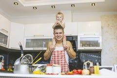 Familj lycklig dotter med farsan i hem- kök som skrattar och pre royaltyfri fotografi