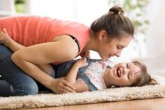 Familj - mamma och dotter som har en gyckel på golv hemma Kvinna och barn som tillsammans kopplar av royaltyfria foton