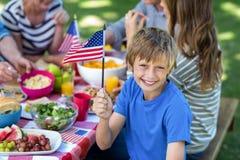 Familj med amerikanska flaggan som har en picknick Royaltyfri Fotografi