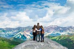 Familj med armar runt om de som tycker om härlig bergsikt på att fotvandra tur Arkivbild