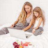 Familj med bärbara datorn i säng royaltyfri bild