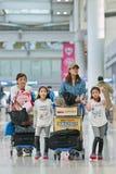 Familj med bagagespårvagnar på den Icheon flygplatsen, Seoul, Sydkorea Arkivfoton