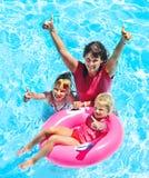 Familj i simbassäng. Arkivfoto