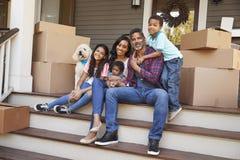 Familj med barn och yttersidahus för älsklings- hund på rörande dag royaltyfri foto