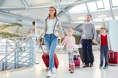 Familj med barn på ankomst på flygplatsen arkivbild