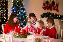 Familj med barn på julmatställen hemma royaltyfri foto