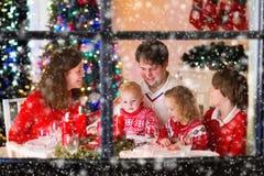 Familj med barn på julmatställen hemma arkivfoto