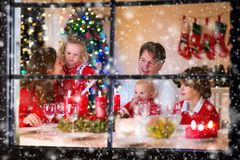 Familj med barn på julmatställen hemma arkivfoton