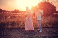 Familj med barn på solnedgången royaltyfria foton