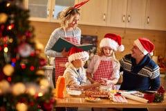 Familj med barn som förbereder kakor för Xmas royaltyfria foton