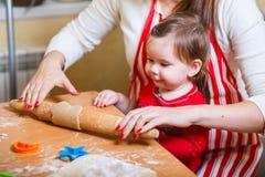 Familj med barn som förbereder kakor för Xmas i kök arkivfoton