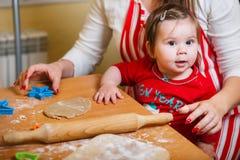 Familj med barn som förbereder kakor för Xmas i kök arkivbilder